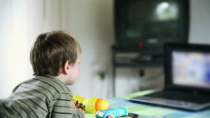 stock-footage-little-boy-watching-cartoons-at-laptop-and-eating-apples
